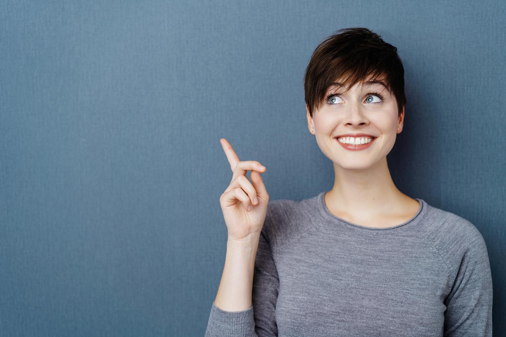 Cheerful new female teacher pointing upwards