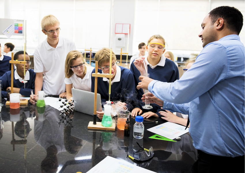 Male secondary school science teacher demonstrating an experiment to the class