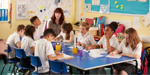 Primary classroom with female teacher and pupils sat round a table