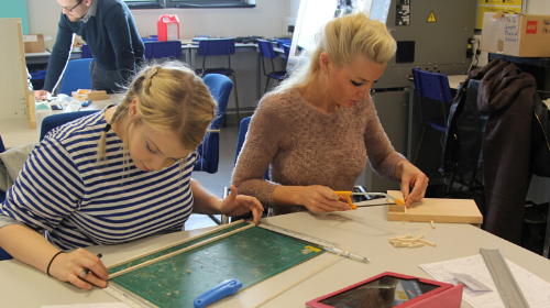 Two teachers measuring and cutting wood in a classroom