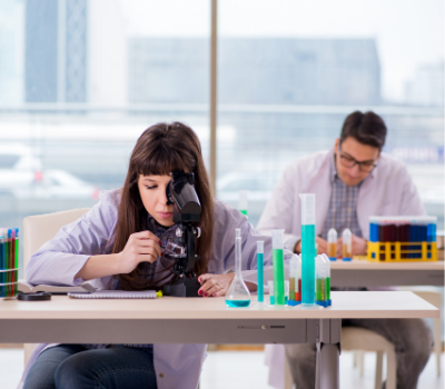 Female looking into microscope on work experience